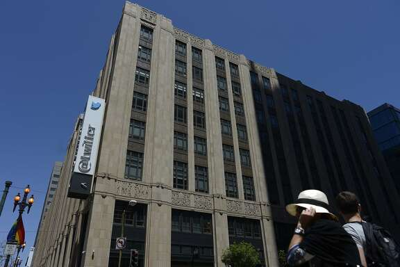 A lady hold onto her hat as she crosses the 10th and Market Street in front of Twitter HQ in San Francisco, California, on Thursday, June 11, 2015.