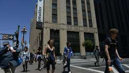 Pedestrians walk across 10th and Market Street in front of Twitter HQ in San Francisco, California, on Thursday, June 11, 2015.