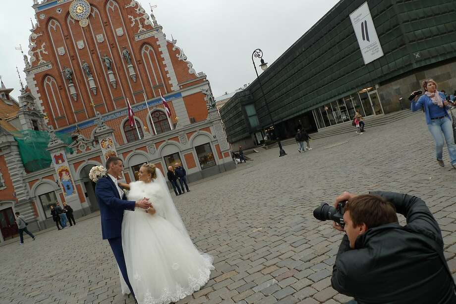 A couple poses for wedding pictures on Town Square, in front of the House of the Blackheads in Riga, Latvia. Photo: Spud Hilton