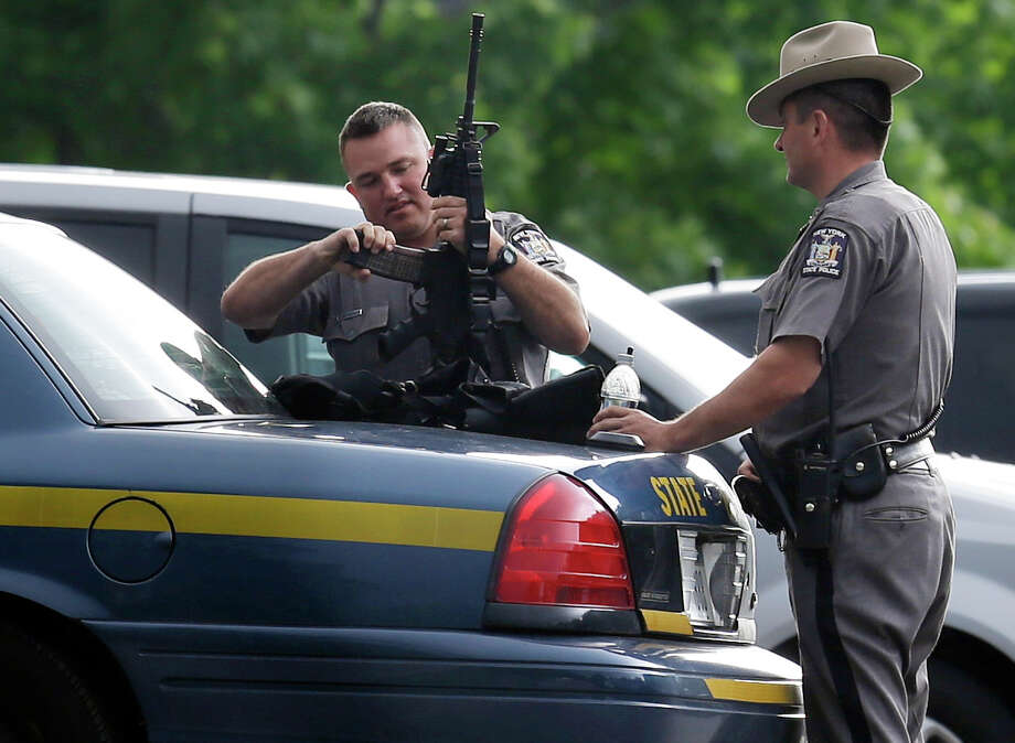 New York State Police prepare their equipment during a search for two escaped prisoners near Dannemora, N.Y., Thursday, June 11, 2015. Police have blocked off the main road outside a northern New York village as authorities concentrate their sixth day of searching for David Sweat and Richard Matt on a swampy area just a couple miles from the prison the convicts broke out of last weekend. Photo: Seth Wenig /Associated Press / AP