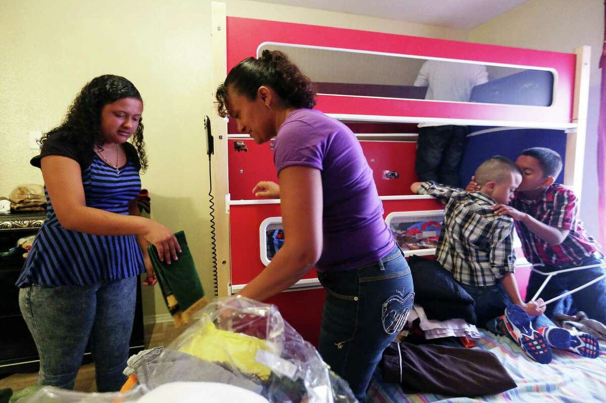 Kimberly Lopez, 13, and mother Gladys Torres fold clothes while son Joel Macario, 6, receives a kiss from brother Junior Macario, 8, in their new apartment on Monday, June 8, 2015, in Houston. Torres was fearing for the safety of her son Carlos Lopez and daughter Kimberly Lopez who were living in area of Honduras increasingly terrorized by gangs. Recently, they were granted special immigrant juvenile status and allowing them to stay here legally. ( Mayra Beltran / Houston Chronicle )