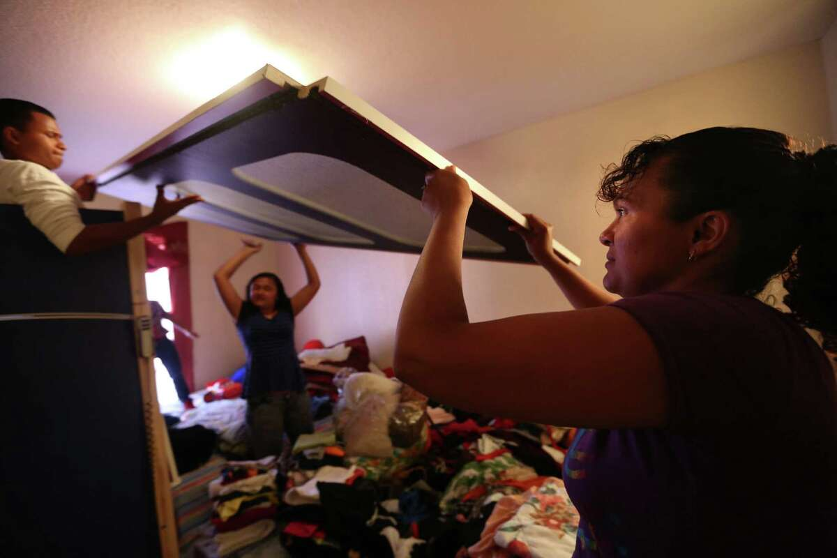 Gladys Torres gets help from son Carlos Lopez, 15, and daughter Kimberly Lopez, 13, building a bed for special needs son in their Houston apartment on Monday, June 8, 2015, in Houston. Torres was fearing for the safety of her son and daughter who were living in area of Honduras increasingly terrorized by gangs. Recently, they were granted special immigrant juvenile status and allowing them to stay here legally. ( Mayra Beltran / Houston Chronicle )