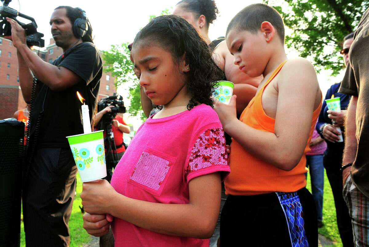 Amarily Franqui, 7, and her brother David Colon, 8, attend a candlelight vigil outside the Trumbull Gardens Community Center on Trumbull Avenue in Bridgeport, Conn., on Thursday June 11, 2015. A shooting at 1 a.m. in a parking lot across the street from the center, left one man dead and seven others injured.