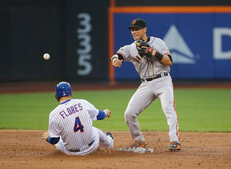 Joe Panik tries to turn a double play for the Giants as Wilmer Flores of the Mets slides into second base at Citi Field. Photo: Al Bello, Getty Images