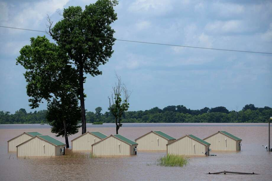 Several cabins at the Red River South Marina in Bossier Parish, La., are submerged in floodwaters Thursday,  June 11, 2015.  Flooding from the swelling Red River put hundreds of homes and farmland underwater or in danger in rural northwest Louisiana, and state officials said Thursday that they would seek a federal disaster declaration to get help for residents. (Douglas Collier/The Shreveport Times via AP) MAGS OUT; MANDATORY CREDIT SHREVEPORTTIMES.COM;  NO SALES Photo: Douglas Collier/The Times, MBO / Associated Press / The Times Shreveport