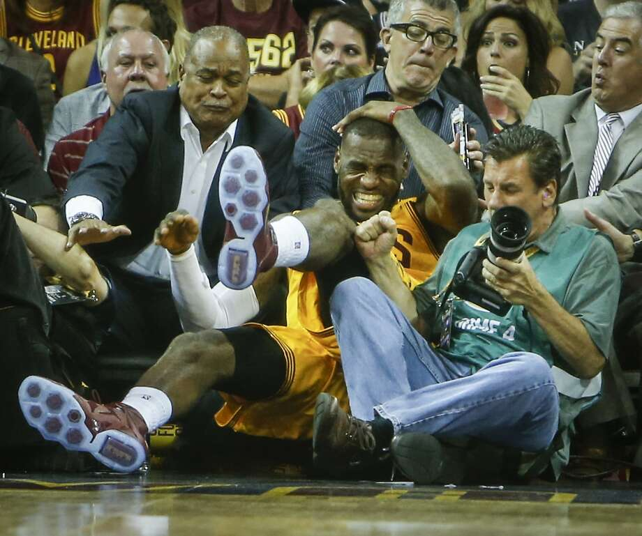 Cleveland Cavaliers' LeBron James grabs his head as he falls into the crowd in the second period during Game 4 of The NBA Finals between the Golden State Warriors and Cleveland Cavaliers at The Quicken Loans Arena on Thursday, June 11, 2015 in Cleveland, Ohio. Photo: Scott Strazzante, The Chronicle