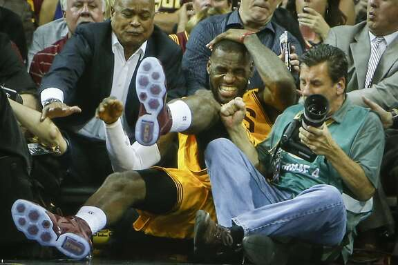 Cleveland Cavaliers' LeBron James grabs his head as he falls into the crowd in the second period during Game 4 of The NBA Finals between the Golden State Warriors and Cleveland Cavaliers at The Quicken Loans Arena on Thursday, June 11, 2015 in Cleveland, Ohio.
