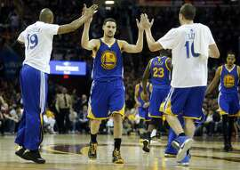 Golden State Warriors' Klay Thompson high fives David Lee and Marreese Speights in 4th quarter of 103-82 win over Cleveland Cavaliers during Game 4 of NBA Finals' at Quicken Loans Arena in Cleveland, Ohio, on Thursday, June 11, 2015.