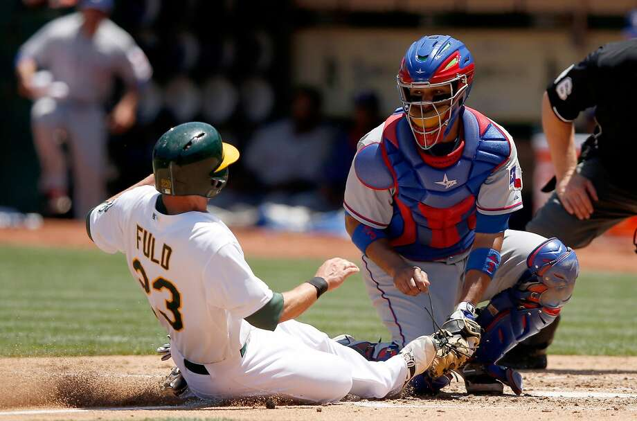 OAKLAND, CA - JUNE 11:  Carlos Corporan #3 of the Texas Rangers tags out Sam Fuld #23 of the Oakland Athletics as he tries to score from third base on a fly-out hit by Josh Reddick #22 in the fifth inning at O.co Coliseum on June 11, 2015 in Oakland, California.  (Photo by Ezra Shaw/Getty Images) Photo: Ezra Shaw, Getty Images