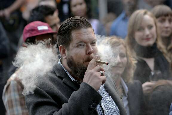 Nicholas Smilgys, director of operations at flowkana smokes during the event as marijuana farmers from California's Emerald Triangle entertain big city customers during a food-and-weed sampling event at a Cole Valley home in San Francisco, Calif., as seen on Thurs. June 11, 2015.