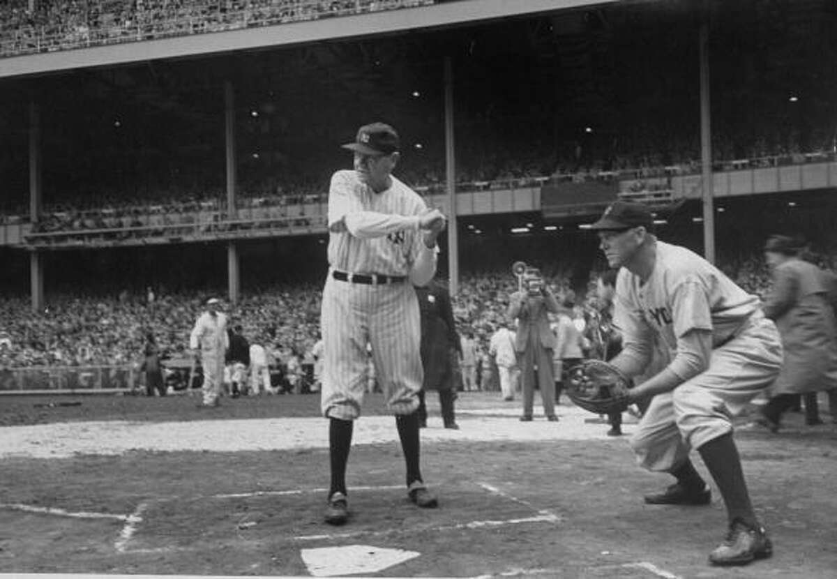 Babe Ruth (L) taking a practice hit at the New York Yankee's 25th Anniversary.
