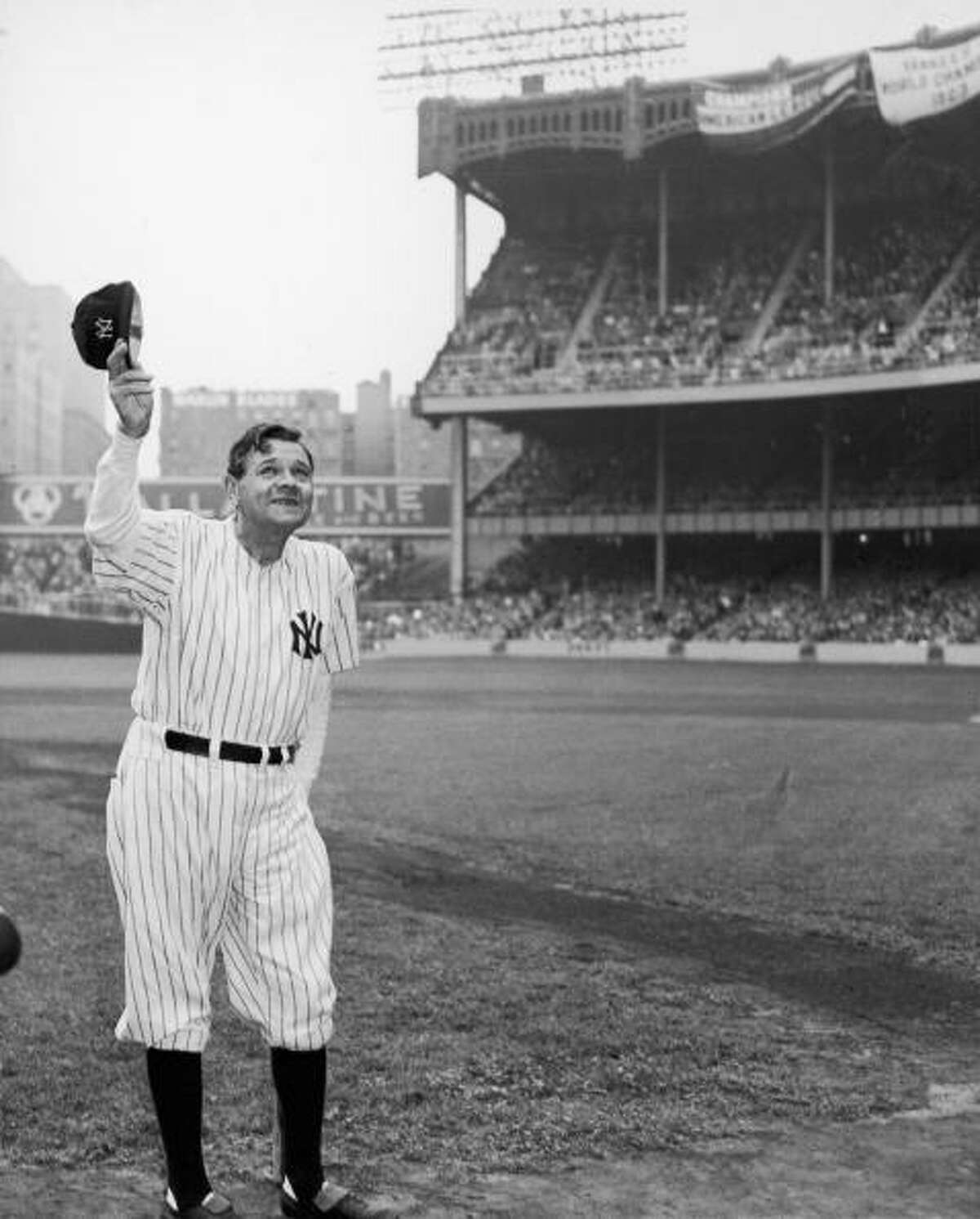 American baseball player Babe Ruth (1895 - 1948) (born George Herman Ruth Jr), dressed in his old New York Yankees number (#3), waves to the crowd during a reunion of Yankee All-Stars at Yankee Stadium, New York, New York, June 16, 1948. Ruth, suffering at the time from cancer and using a baseball bat as a cane (barely visible behind him), died two months later.