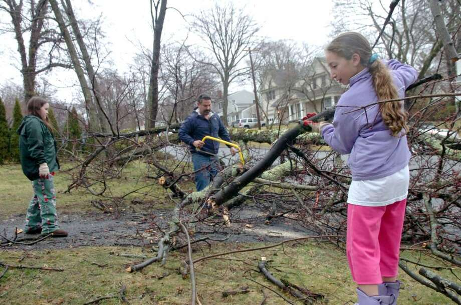 Phil Brous helped cut apart the fallen tree of a neighbor, on McArthur Drive, after the strom.  He had help from his daughter Kathryn 11, left and friend Marissa Brooks, 11, right, on Sunday, March 14, 2010.  The house belonged to the Brooks family. Photo: Helen Neafsey / Greenwich Time
