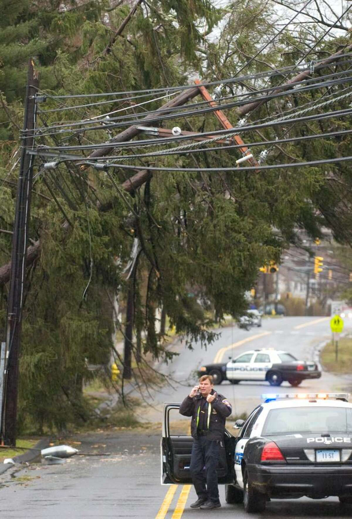 Sgt. Paul Guzda talks on the phone as he blocks Newfield Ave. near Fifth as Stamford recovers from the Saturday's storm.