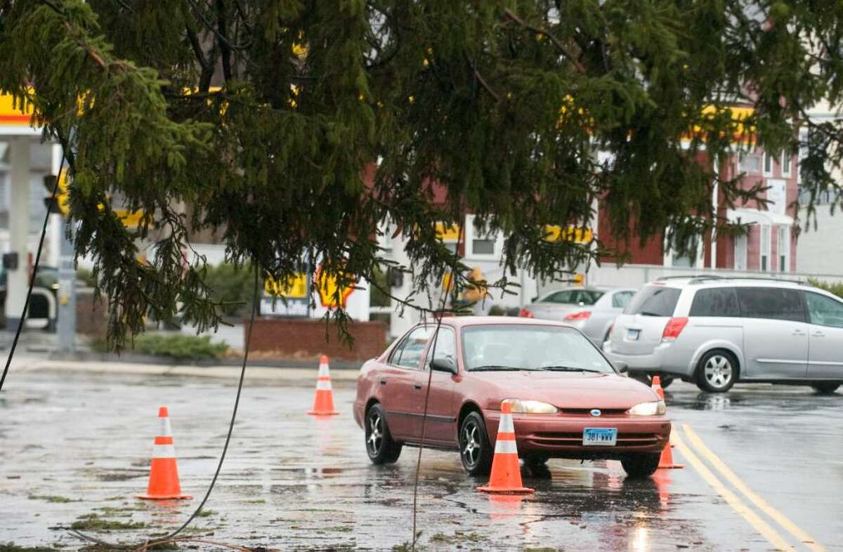 A motorist maneuvers around a downed tree on Hope St. as Stamford recovers from the Saturday's storm.