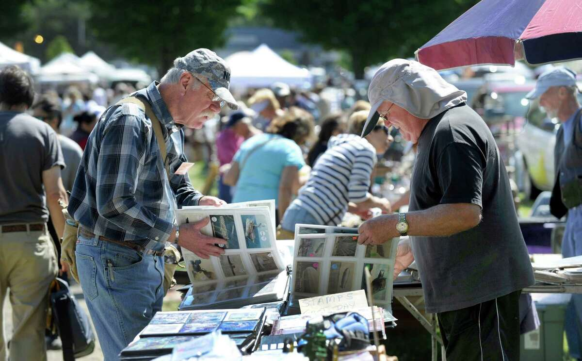 Bruce Nielsen, left, of Southington, and Karl Hermonat, of New Milford, who sells antique papers at The Elephant's Trunk Country Flea Market, look through albums of World War II postcards.