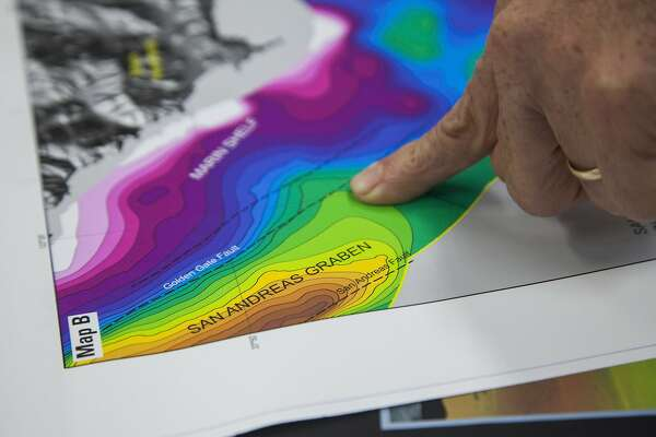 Geophysicist Samuel Johnson checks out the new maps at the U.S. Geological Survey's Marine Geology Mapping center, Thursday, June 11, 2015, in Santa Cruz, Calif. Johnson led the mapping project that shows seismic fault hazards, marine habitats, rocky shoals and submarine environments off the coasts of San Francisco and other Northern California areas.