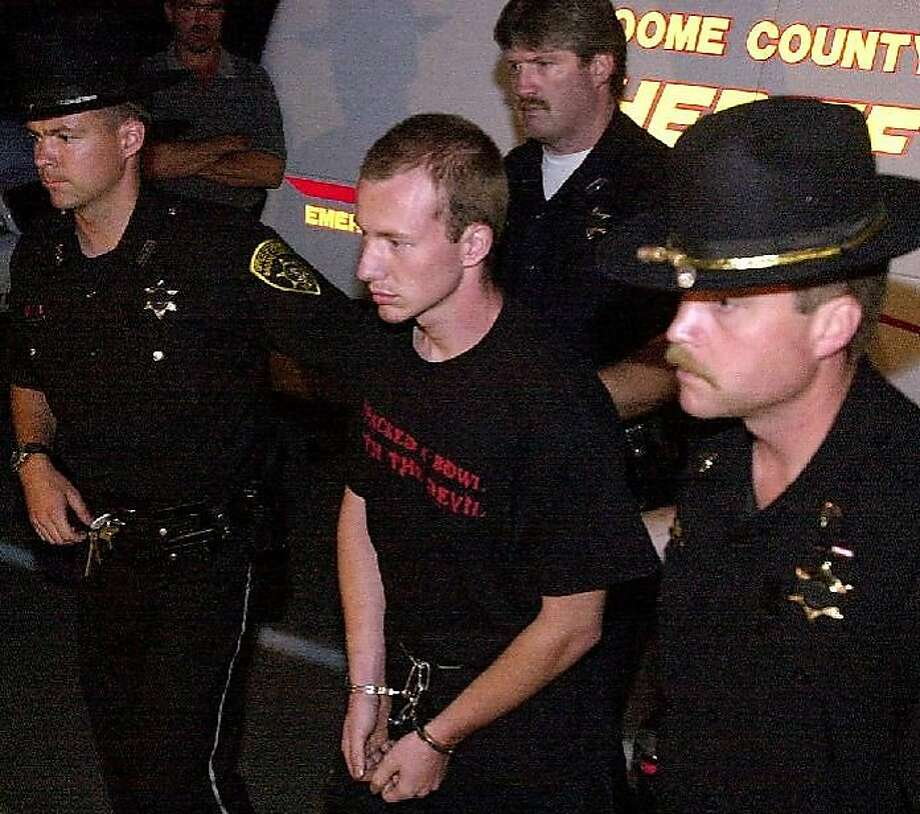 """In this July 6, 2002 photo, law enforcement officers escort David Sweat, 22, in handcuffs, in Broome County, N.Y., after his arrest in connection with the death of sheriff's Deputy Kevin J. Tarsia. Sweat was serving a sentence of life without parole at the Clinton Correctional Facility in Dannemora, N.Y., for the killing of Tarsia when he and another prisoner escaped the maximum-security prison near the Canadian border over the weekend. Authorities say Sweat, 34, and Richard Matt, 48, cut through steel walls at the back of their adjacent cells and sliced through steel pipes while making their """"Shawshank Redemption""""-style breakout, which guards discovered early Saturday, June 6, 2015. Photo: Suzie O'Rourke, Associated Press"""