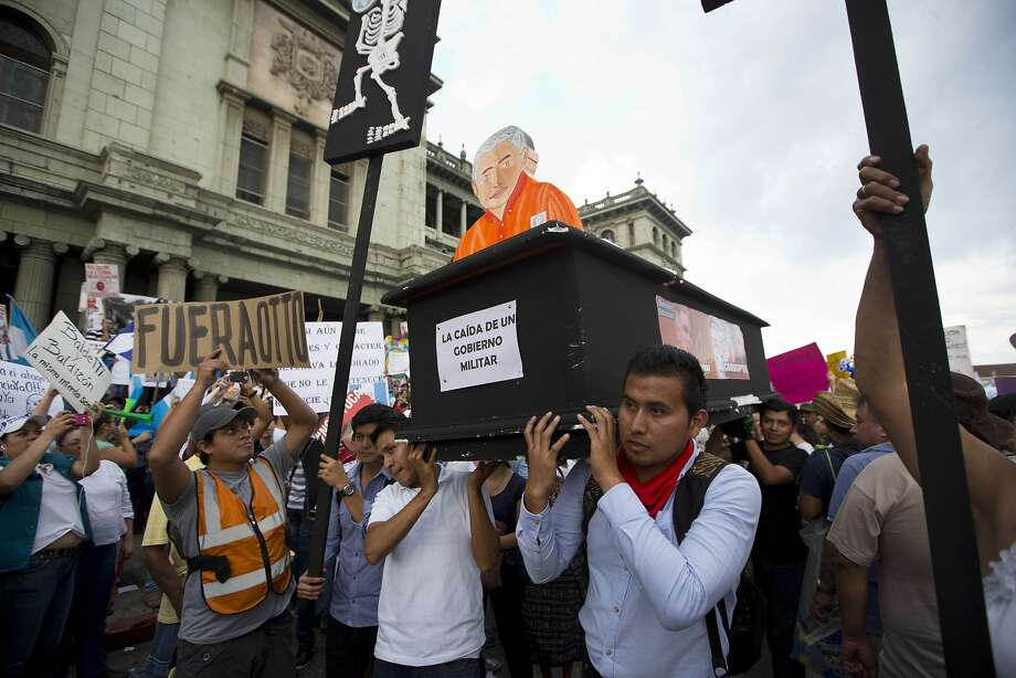 Protesters carry a fake coffin with an effigy of President Otto Perez Molina during a demonstration to demand his resignation in Guatemala City. Photo: Moises Castillo, Associated Press