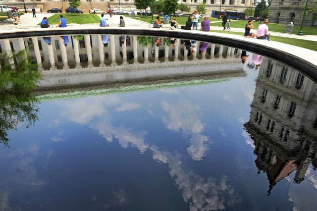 The New York State Education Building and Capitol are reflected in the fountain pool of the West Capitol Park during lunchtime on Friday June 12, 2015 in Albany , N.Y.  (Michael P. Farrell/Times Union) Photo: Michael P. Farrell / 00032271A