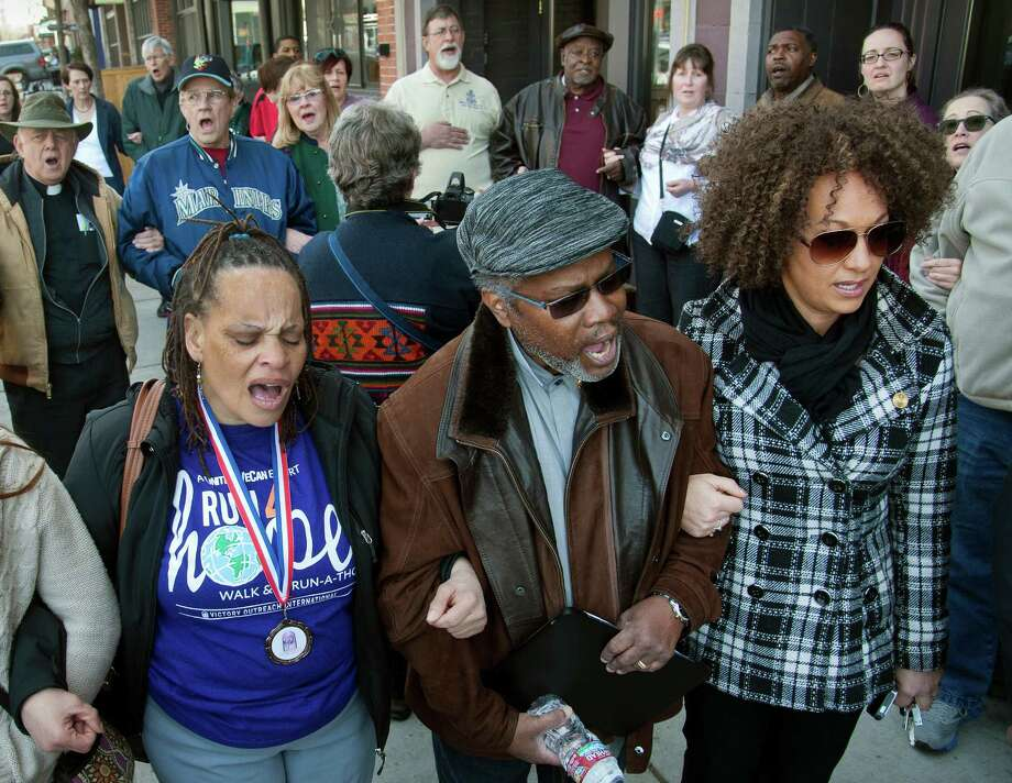 """FILE - In this Friday, March 6, 2015, file photo, from left, Della Montgomery-Riggins, Charles Thornton and Spokane NAACP president Rachel Dolezal link arms and sing """"We Shall Overcome"""" at a rally in downtown Spokane, Wash., responding to a racist and threatening package received by Dolezal. Dolezal is now facing questions about whether she lied about her racial identity, with her family saying she is white but has portrayed herself as black. (Dan Pelle/The Spokesman-Review via AP, File) Photo: Dan Pelle, MBI / Associated Press / The Spokesman-Review"""