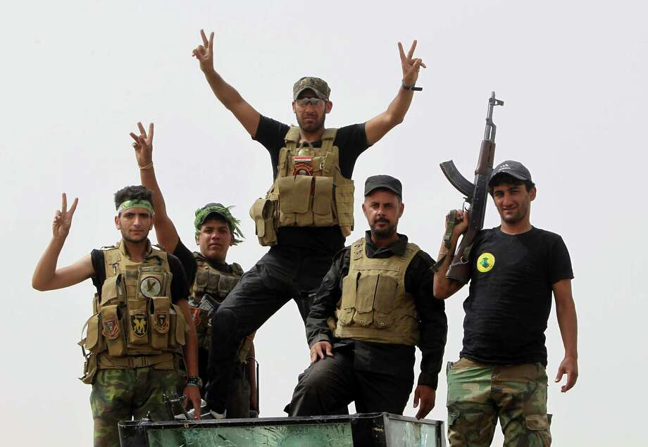 "Iraqi Shiite fighters from the Popular Mobilisation units flash the ""V"" for victory sign in the town of Baiji, north of Tikrit, as they fight alongside Iraqi forces against the Islamic State (IS) jihadist group to try to retake the strategic northern Iraqi town for a second time, on June 10, 2015. Baghdad regained control of Baiji -- located on the road to IS hub Mosul and near the country's largest oil refinery -- last year, but subsequently lost it again. AFP PHOTO / AHMAD AL-RUBAYEAHMAD AL-RUBAYE/AFP/Getty Images Photo: AHMAD AL-RUBAYE, Staff / AFP / Getty Images / AFP"