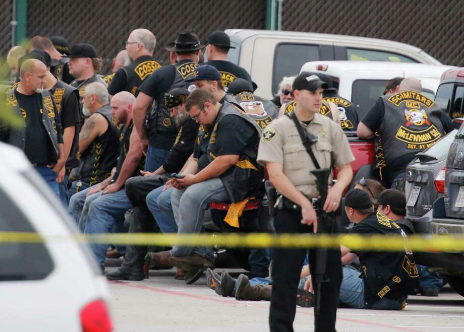 FILE - In this May 17, 2015 file photo, a McLennan County deputy stands guard near a group of bikers in the parking lot of a Twin Peaks restaurant in Waco, Texas.  The prevailing images of protests in Baltimore and Ferguson, Missouri, over police killings of black men were of police in riot gear, handcuffed protesters, tear gas and mass arrests. The main images of a fatal gun battle between armed bikers and police in Waco, Texas, also showed mass arrests _ carried out by nonchalant-looking officers sitting around calm bikers on cell phones.  (Rod Aydelotte/Waco Tribune-Herald via AP) Photo: Rod Aydelotte, MBO / Associated Press / Waco Tribune-Herald