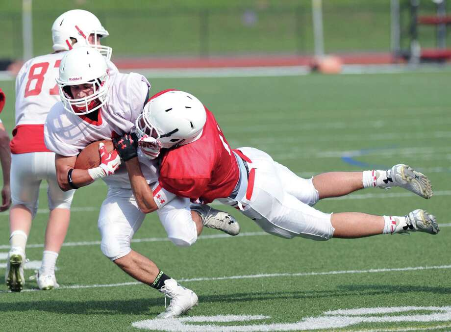 At left, white team receiver Anthony Ferraro, runs upfield after making a reception as red defender Joey Longo dives to make the tackle during the Red vs. White Greenwich High School football scrimmage at the school in Greenwich, Conn., Friday, June 12, 2015. Photo: Bob Luckey, Hearst Connecticut Media / Greenwich Time
