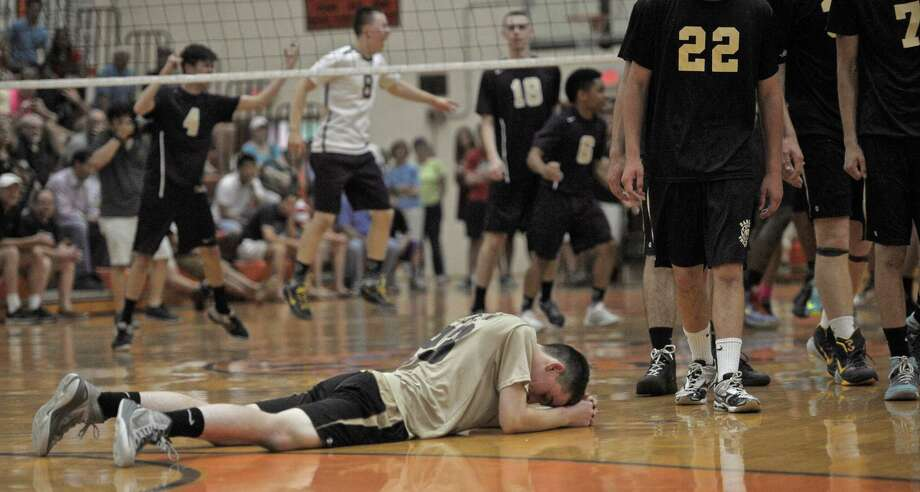 Joel Barlow High School's Dan Dolan (23) lays on the court as Newington High School players celebrate winning the boys Class M state volleyball championship three games to one on Friday, June 12, 2015, at Shelton High School, Shelton, Conn. Photo: H John Voorhees III, Hearst Connecticut Media / The News-Times