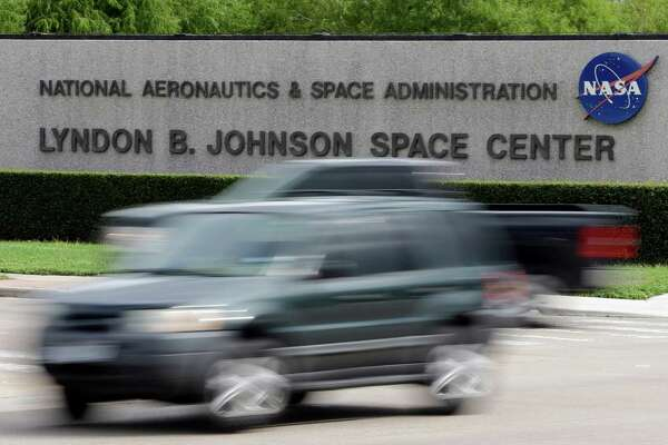Cars pass by NASA's Johnson Space Center Tuesday, Oct. 1, 2013, in Houston. Most of the space center's employees are now on furlough because of the partial government shutdown. Those working to support the international space station continue to work. Congress plunged the nation into a partial government shutdown Tuesday as a long-running dispute over President Barack Obama's health care law stalled a temporary funding bill, forcing about 800,000 federal workers off the job and suspending most non-essential federal programs and services. (AP Photo/David J. Phillip)
