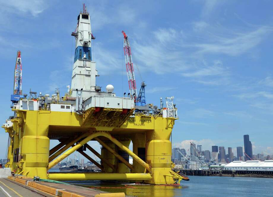 Seattle's skyline provides the backdrop for the Transocean Polar Pioneer as it is loaded with supplies in the city's port in May. Shell expects thick ice at the sites of its offshore Alaska wells until late July. Photo: Jennifer A. Dlouhy / Houston Chronicle