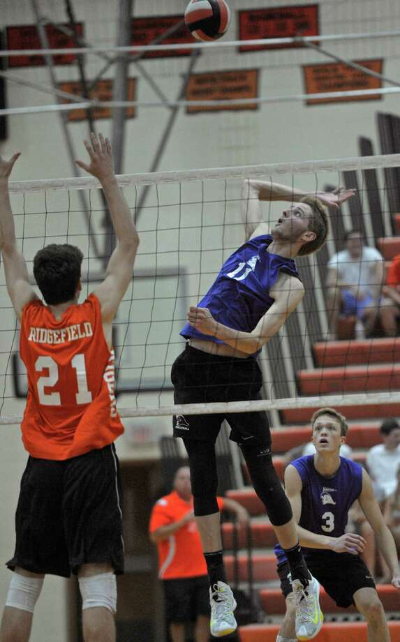 Darien's Alex Preston (11) goes up for the spike while Ridgefiled's RyanMiller (21) goes up for the block during the boys Class L state volleyball championship game between Darien and Ridgefield high schools, on Friday, June 12, 2015, at Shelton High School, Shelton, Conn. Photo: H John Voorhees III, Hearst Connecticut Media / The News-Times