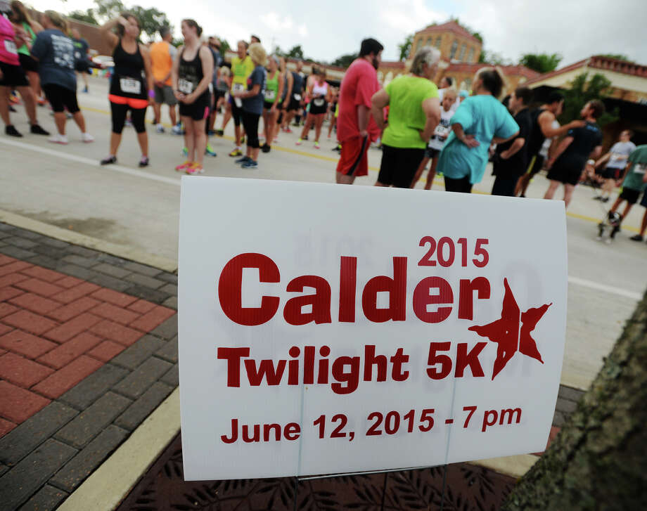 Runners and walkers gather before the start of Friday's 5K on Calder Avenue. The 2015 Calder Twilight 5K Run/Walk garnered a crowd of around 350-400 participants Friday evening.  Photo taken Friday 6/12/15 Jake Daniels/The Enterprise Photo: Jake Daniels / ©2015 The Beaumont Enterprise/Jake Daniels