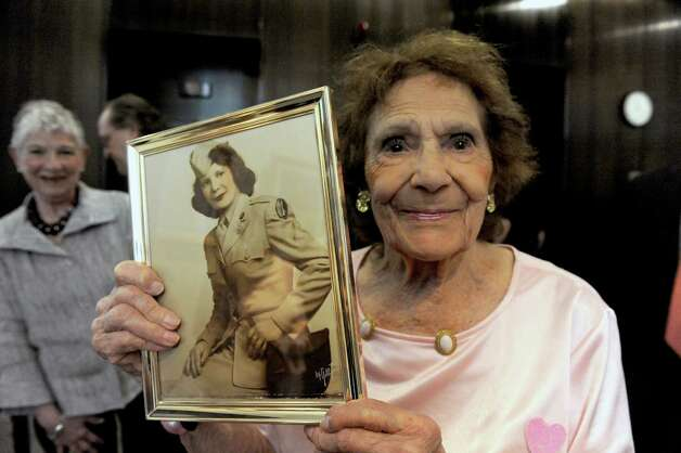 90-year-old World War II veteran Josephine Smith of Troy holds a photograph of her from the war during a recognition of New York State's women veterans and unveiling of art and artifacts in the New York State Vietnam Memorial Gallery that illustrate women veterans' contributions during the Vietnam War at the Empire State Plaza on Friday June 12, 2015 in Albany , N.Y.  (Michael P. Farrell/Times Union) Photo: Michael P. Farrell / 00032270A
