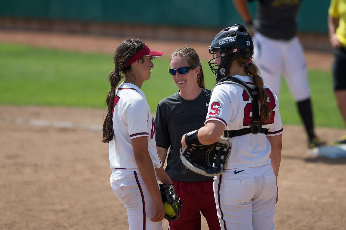 Stanford coach Rachel Hanson talks strategy with pitcher Erin Ashby and catcher Jessica Plaza.