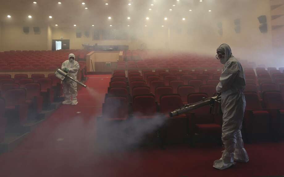 Workers wearing protective gears spray antiseptic solution as a precaution against the spread of MERS, Middle East Respiratory Syndrome, virus at an art hall in Seoul, South Korea, Friday, June 12, 2015. The outbreak of Middle East respiratory syndrome has caused panic in South Korea. Photo: Lee Jin-man, Associated Press