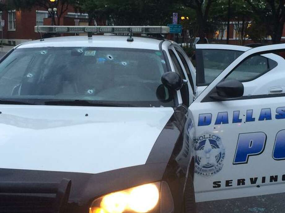 This photo sent via Twitter by the Dallas Police Department shows gunshot damage to a squad car Saturday, June 13, 2015, in Dallas. Multiple gunmen toting automatic weapons opened fire on officers outside Dallas Police headquarters early Saturday morning, before one man fled the scene being chased by police in what witnesses described as an armored van, according to Dallas Police Chief David Brown. (Dallas Police Department, via AP) Photo: Associated Press / Dallas Police Department