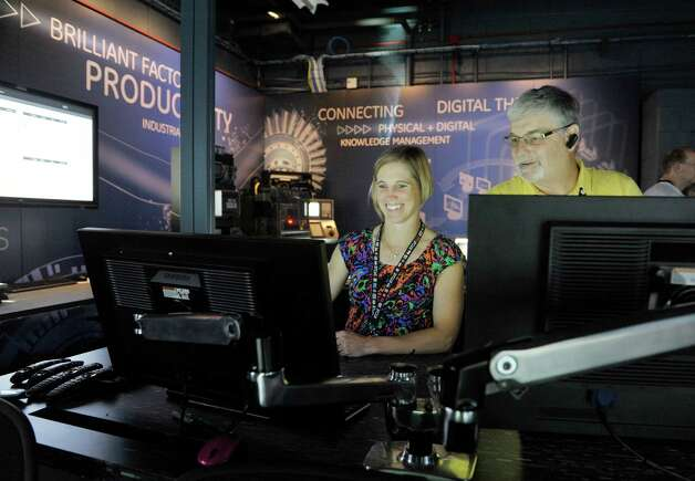 Nicole Vidro, left, a GE manufacturing engineer, and Mike Herzog, a GE process specialist, work in the Brilliant Factory at the GE Global Research Center on Tuesday, June 9, 2015, in Niskayuna, N.Y.  The Brilliant Factory is a virtual lab where factory production floors can be created and modified and virtual equipment can be created.    (Paul Buckowski / Times Union) Photo: PAUL BUCKOWSKI / 00032209A