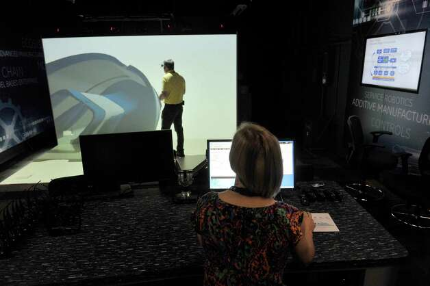 Nicole Vidro, foreground, a GE manufacturing engineer, and Mike Herzog, a GE process specialist, work with CAVE, a 3D virtual environment in the Brilliant Factory at the GE Global Research Center on Tuesday, June 9, 2015, in Niskayuna, N.Y.  On the screen is a representative piece of material that Vidro is able, through the use of 3D glasses, to walk around the piece and even walk inside the piece.   The Brilliant Factory is a virtual lab where factory production floors can be created and modified and virtual equipment can be created.    (Paul Buckowski / Times Union) Photo: PAUL BUCKOWSKI / 00032209A