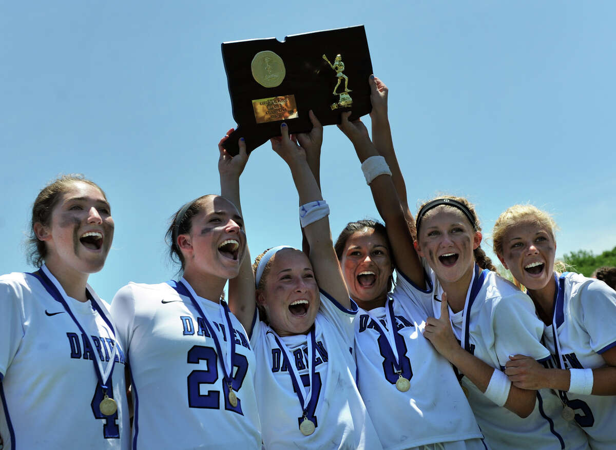 Darien seniors hold up their Class L State Championship plaque after defeating Wilton in the girls lacrosse final Saturday, June, 13, 2015, at Bunnell High School in Stratford, Conn.