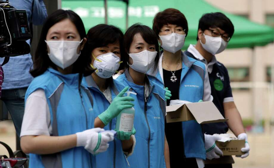 South Korean health workers wearing masks as a precaution against the MERS virus, wait to check examinees' temperature and to sanitize their hands at a test site for a civil service examination in Seoul, South Korea, on Saturday.  Experts from the World Health Organization and South Korea have downplayed concerns about the MERS virus spreading further within the country, but they say it's premature to declare the outbreak over. Photo: Lee Jin-man, STF / AP