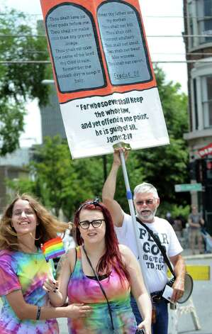 A lone dissenter, who did not give his name, right, heckles parade participants during the Capital PRIDE Parade on Saturday, June 13, 2015, in Albany, N.Y. (Cindy Schultz / Times Union) Photo: Cindy Schultz / 00032232A