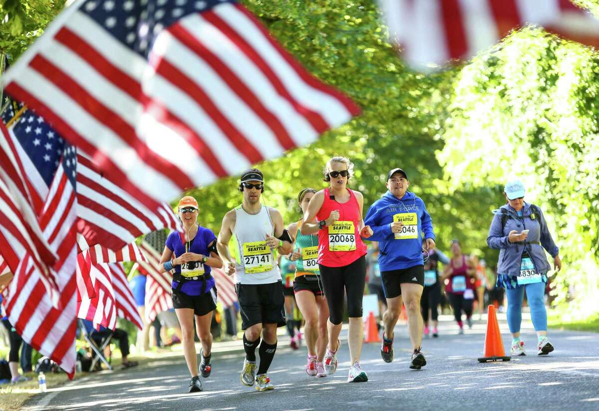 Runners make their way through flags held in honor of lost members of the U.S. military during the annual Rock 'n' Roll Seattle Marathon on Saturday, June 13, 2015. About 18,000 people participated in the annual race that wound its way from the Seattle Center to Mercer Island and back.