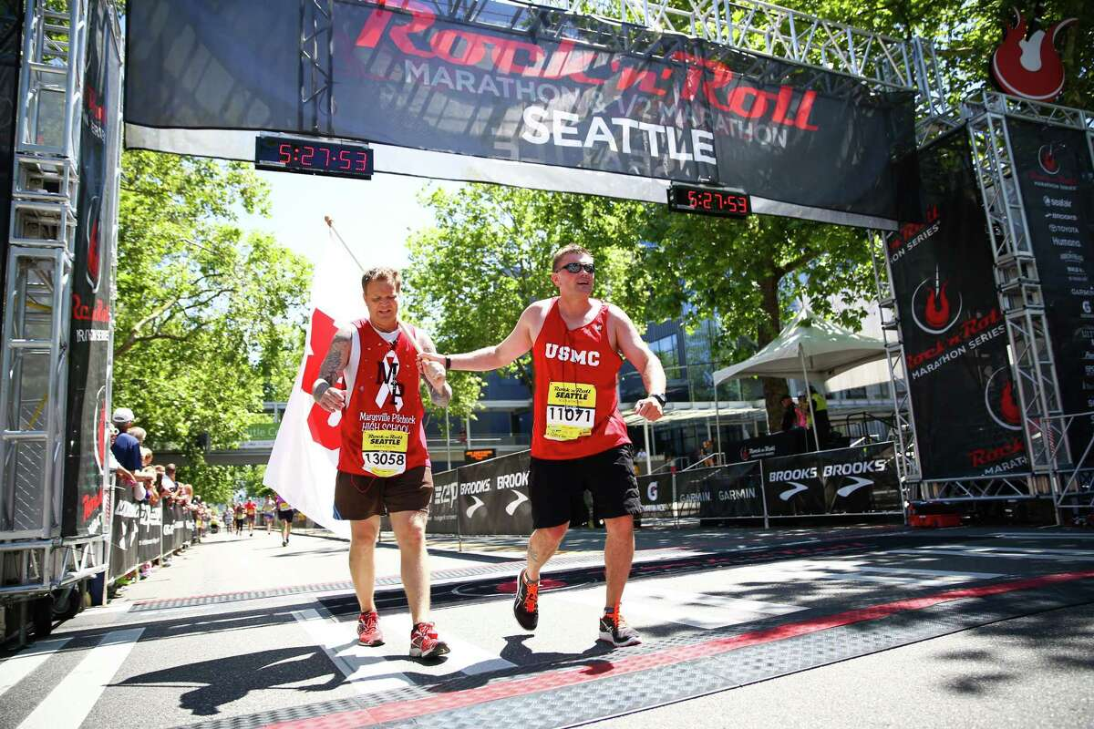 Marysville-Pilchuck High School resource officer Chris Sutherland, left, carries the MPHS flag across the finish line along with his friend, Brian Johnson. Sutherland works as a police officer in the school where a student killed four other students and then himself last October.