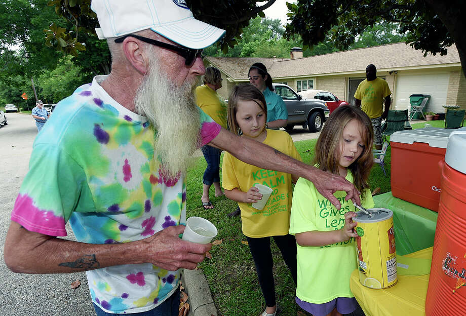 Steve Maxwell, left, of Shreveport, La., drops his tip in the jar for Andria Green, 8, Saturday, June 13, 2015, in Overton, Texas.  8-year-old Andria Green and her 7-year-old sister, Zoey, whose lemonade stand was shut down because they lacked a permit will instead offer the drink for free Saturday in Overton, about 120 miles east of Dallas. Photo: Andrew D. Brosig, Associated Press / Tyler Morning Telegraph