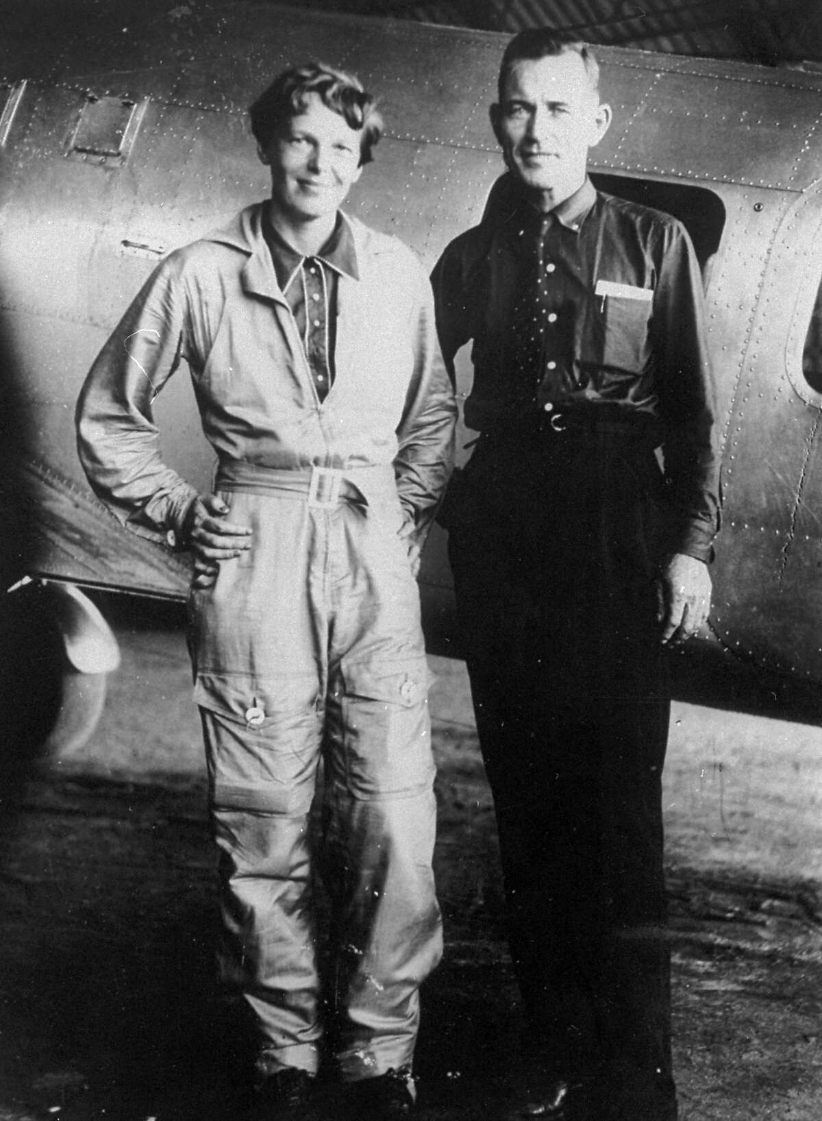 FILE - In this May 1937 file photo, aviator Amelia Earhart and her navigator, Fred Noonan, stand in front of their twin-engine Lockheed Electra airplane in Los Angeles, prior to their historic flight in which Earhart was attempting to become first female pilot to circle the globe. Earhart and her navigator, Fred Noonan, disappeared in the South Pacific in July 1937. (AP Photo/File)