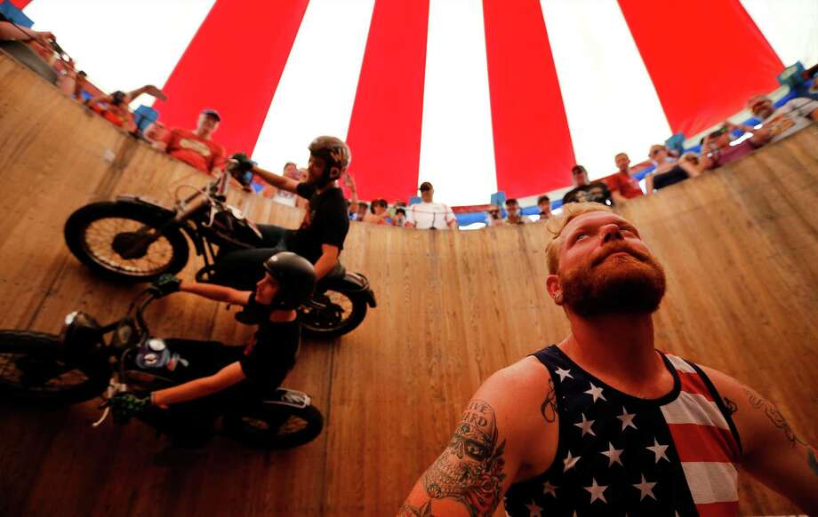 """Jon Lanfair looks up as Cody (top) and Kyle Ives of The Ives Brothers Wall of Death ride along a wooden circular wall at the 20th Annual Republic of Texas Biker Rally in Austin on Saturday, June 13, 2015. Organizers said the event attracts about 38-45,000 visitors a year which features motorcycles of all kinds, concerts and vendors catering to bikers. Though the event has changed from past years by adding events to attract bikers, little else has changed. """"At the heart of it, (the event) is about bikers,"""" said Matt Ceniceros of Media Relations. The event concludes on Sunday. (Kin Man Hui/San Antonio Express-News) Photo: Photos By Kin Man Hui / San Antonio Express-News / ©2015 San Antonio Express-News"""