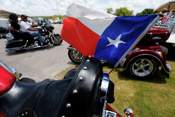 """A Texas flag flies on the back of a motorcycle at the 20th Annual Republic of Texas Biker Rally in Austin on Saturday, June 13, 2015. Organizers said the event attracts about 38-45,000 visitors a year which features motorcycles of all kinds, concerts and vendors catering to bikers. Though the event has changed from past years by adding events to attract bikers, little else has changed. """"At the heart of it, (the event) is about bikers,"""" said Matt Ceniceros of Media Relations. The event concludes on Sunday. (Kin Man Hui/San Antonio Express-News)"""
