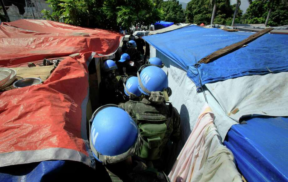 United Nations peacekeepers patrol an earthquake survivors camp in Port-au-Prince in 2010. A Public Radio International report in August said the U.N. mission in Haiti had brought seven women and their children for DNA testing. Photo: Jorge Saenz, STF / AP