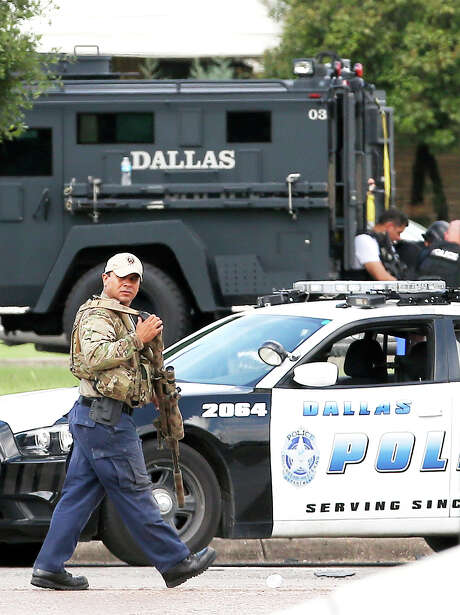 A sniper walks by the intersection of Dowdy Ferry Rd and Interstate 45 during a stand off with a gunman barricaded inside a van near by, Saturday, June 13, 2015, in Hutchins, Texas. The gunman allegedly attacked Dallas Police Headquarters. (AP Photo/Brandon Wade) Photo: Brandon Wade, FRE / Associated Press / FR168019 AP